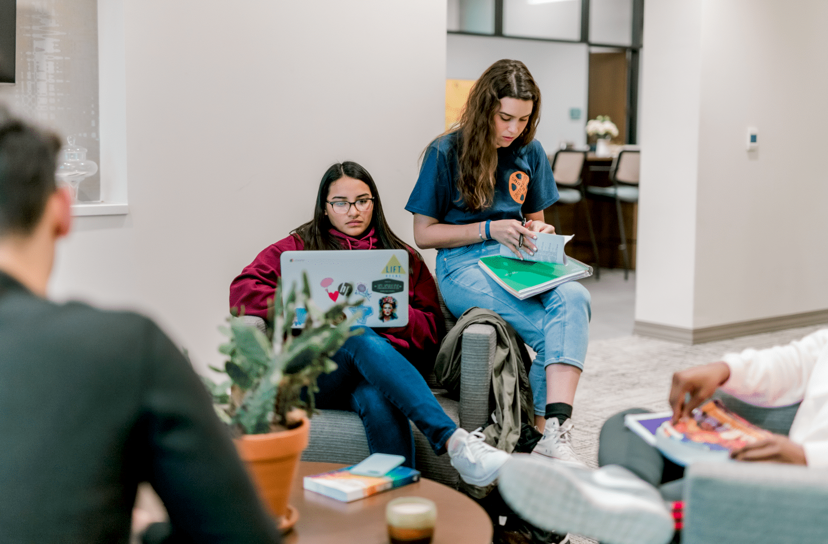 A student sits in a chair and works on her laptop; her peer sits on the armrest of the chair and goes through her notes.