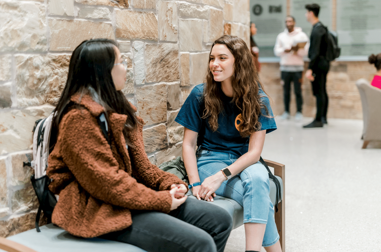 Two female students sit on a bench in front of a light-colored brick wall, smiling and talking