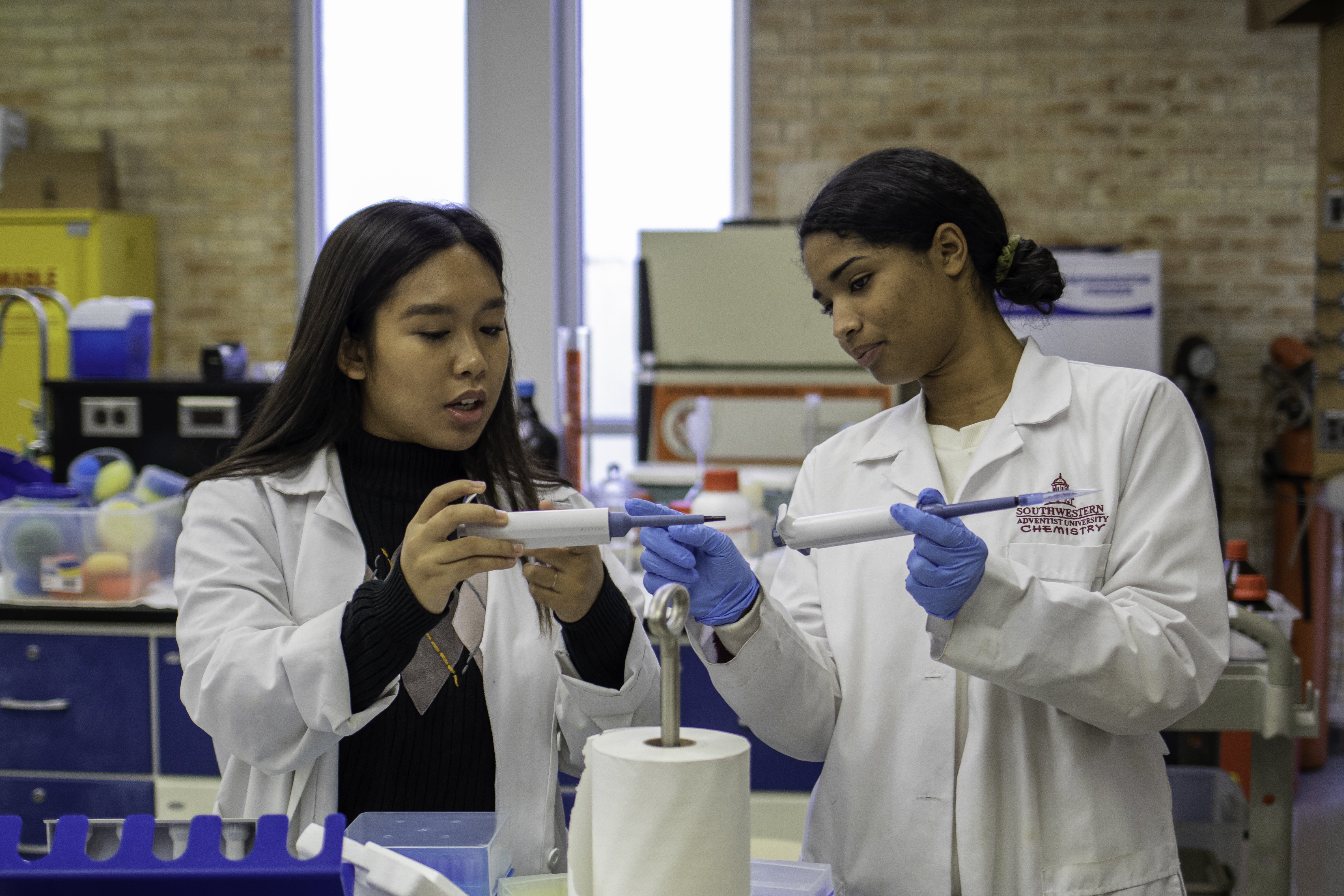 Two students examine and pick up their lab tools as they compare their results with each other.