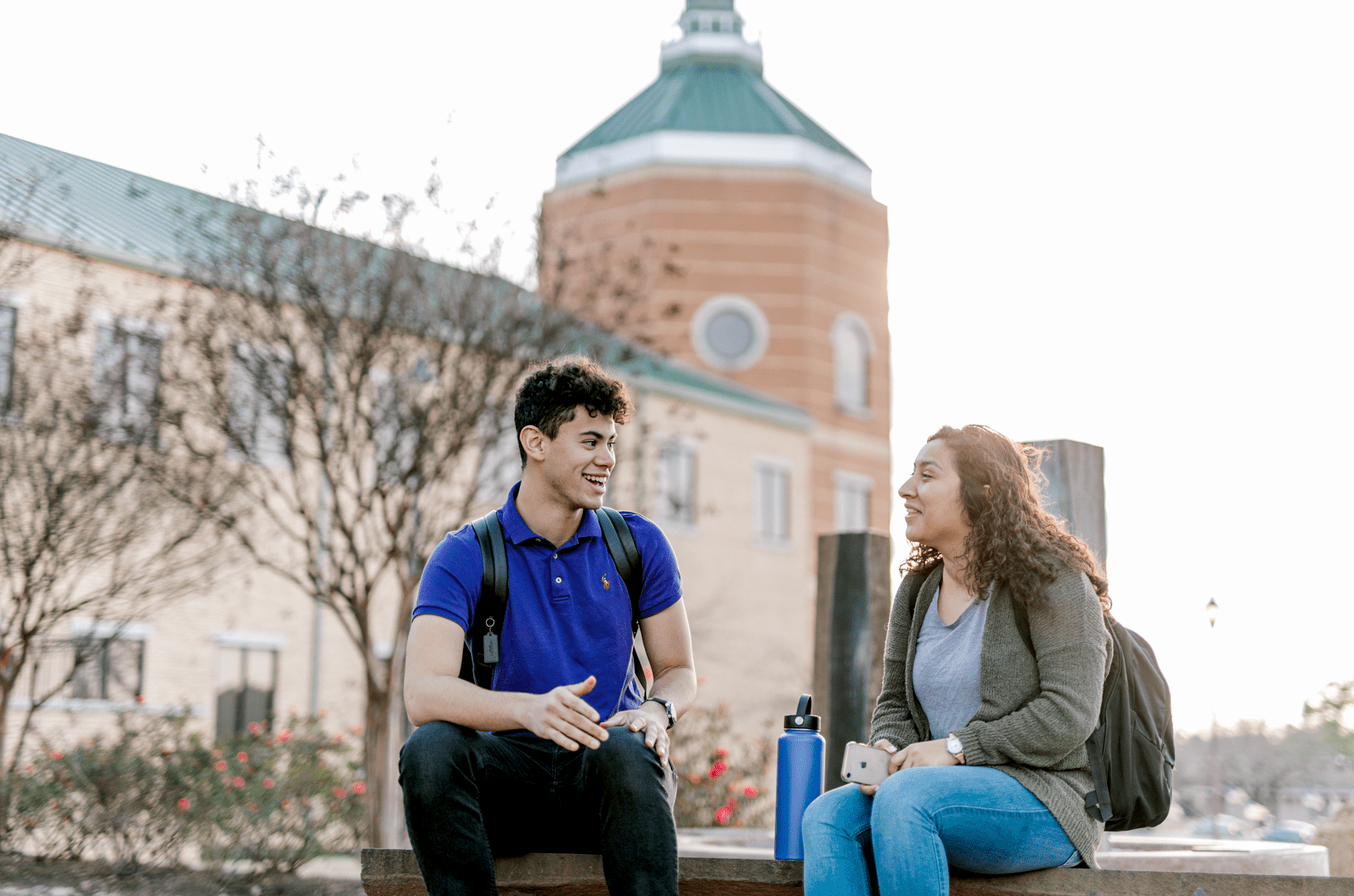 Two students sit together outside while looking at each other, talking and laughing