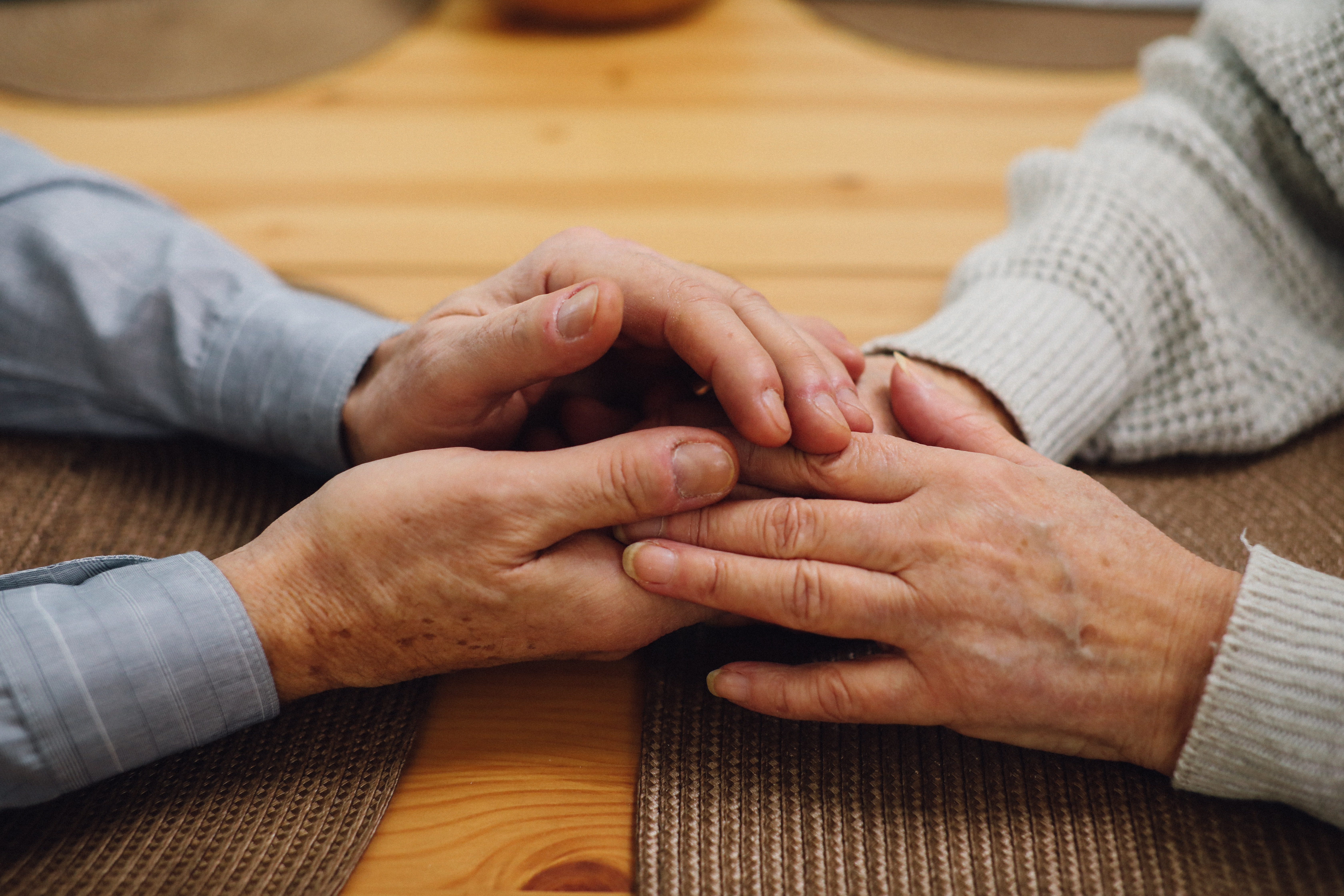Elderly couple holding hands on table with placemats