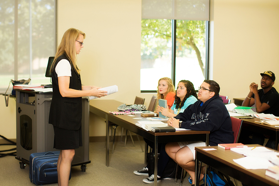 A blonde professor stand in front of the classroom and her students and reads to them from a book as they attentively listen to her teach