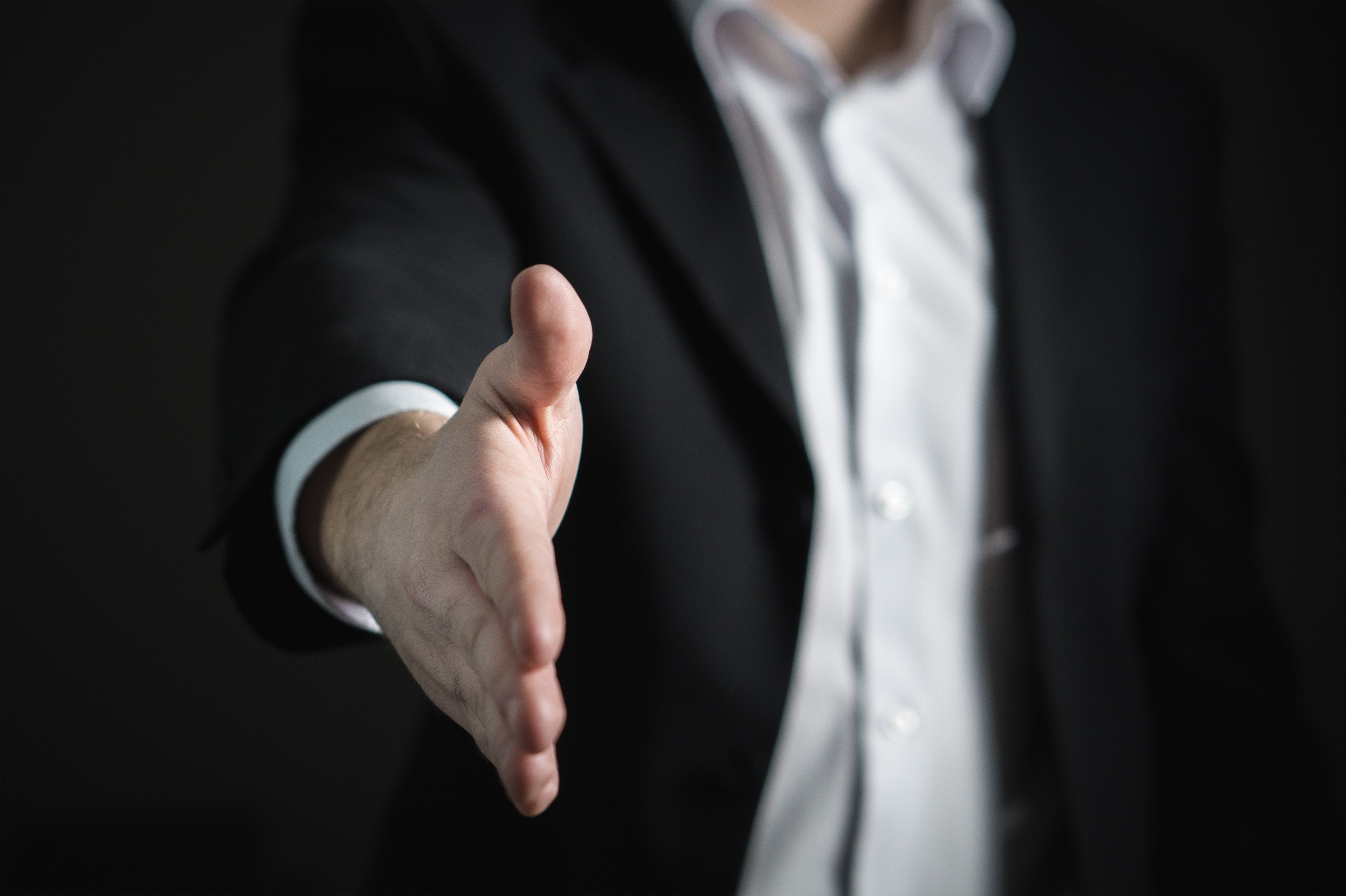 A close up of a man in a suit extending his arm reaching out to shake your hand