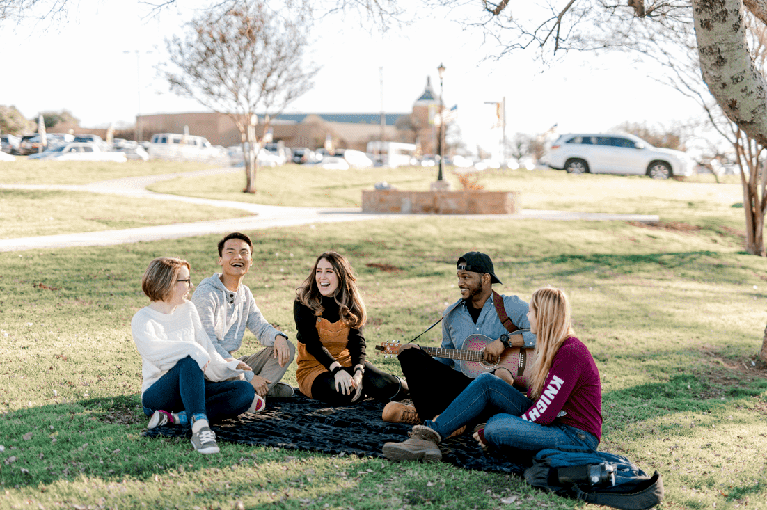 A group of students sit togther smiling and playing guitar on campus on the grass.