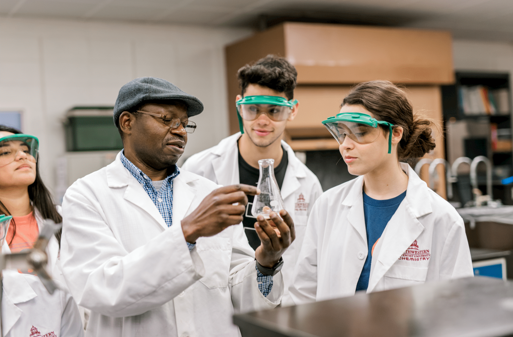 A professor holds up a flask as he points and explains something to his students. All of them are wearing lab coats while the students all wear goggles.