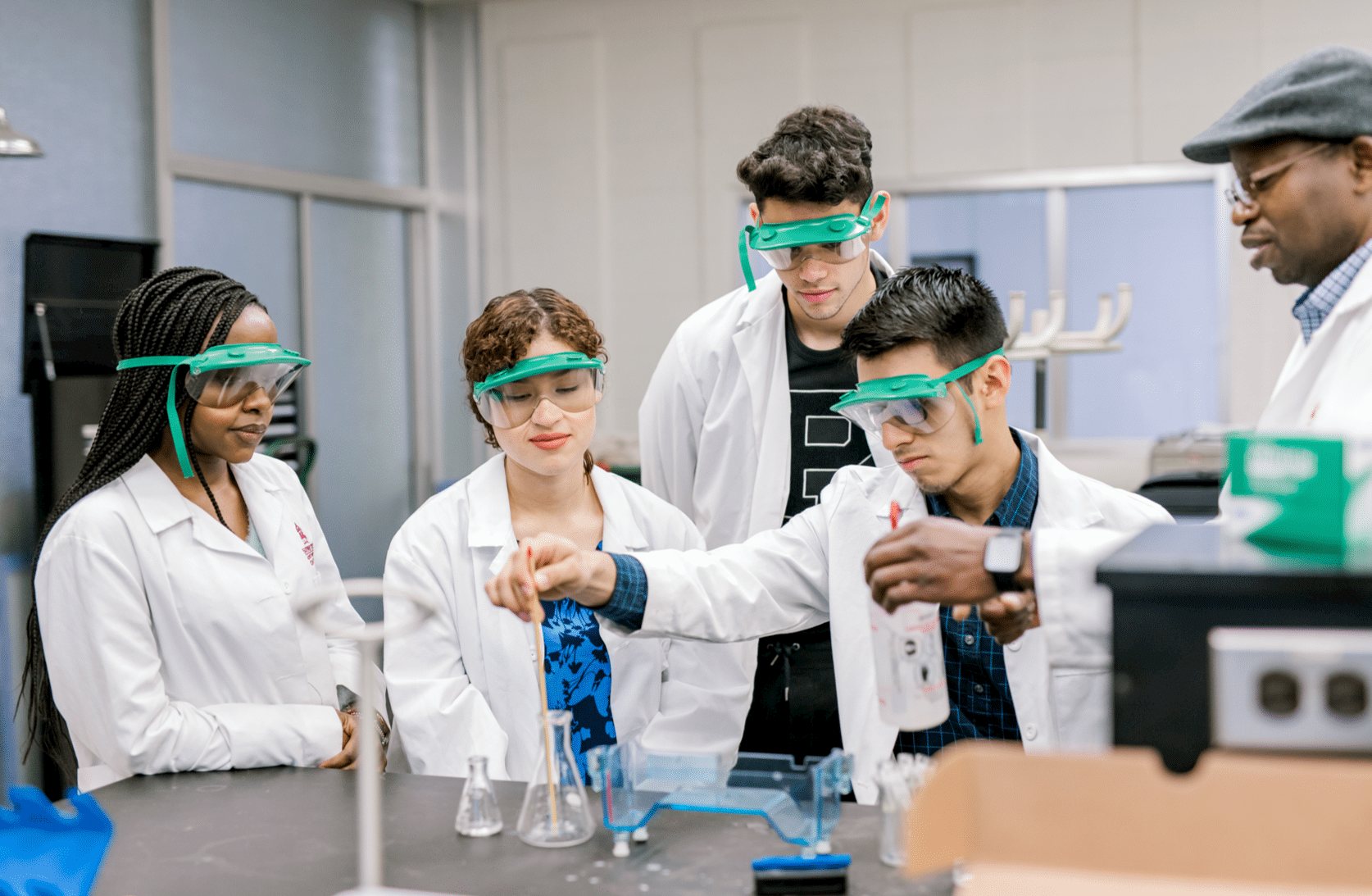 A student begins to mix something in a flask as his peers and professor stand around in observation.