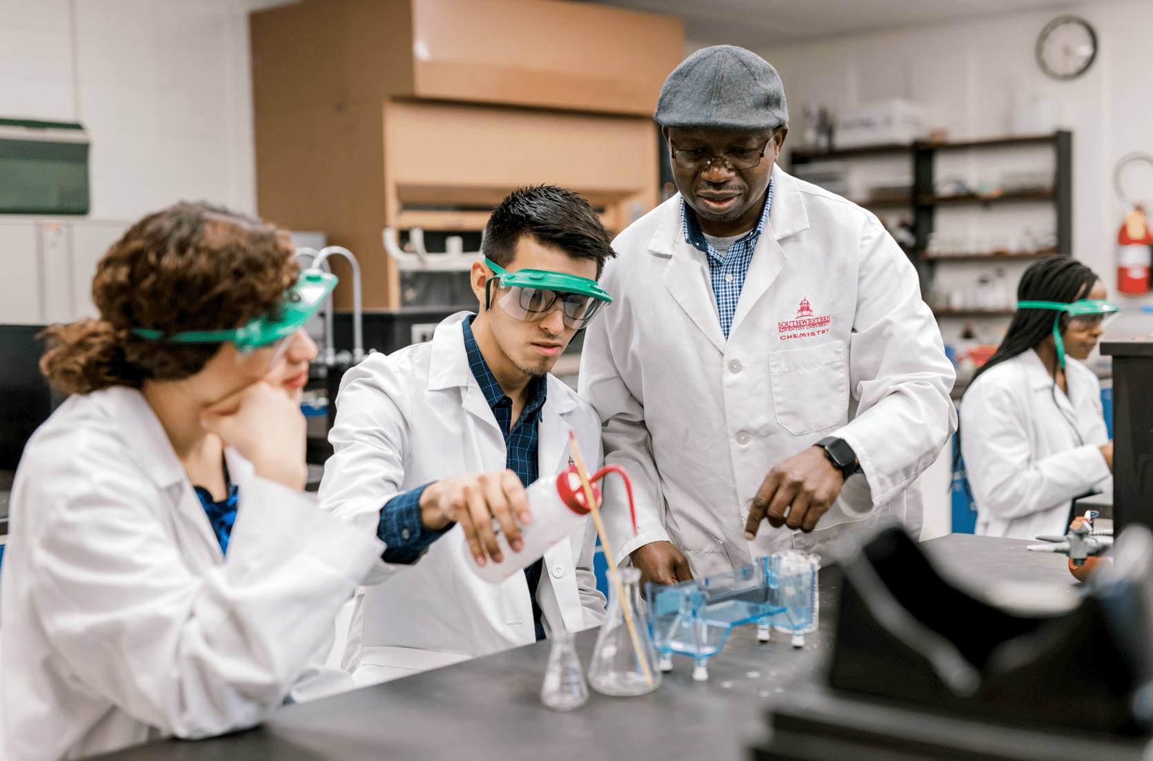 Group of students with lab coats in lab analyzing class materials