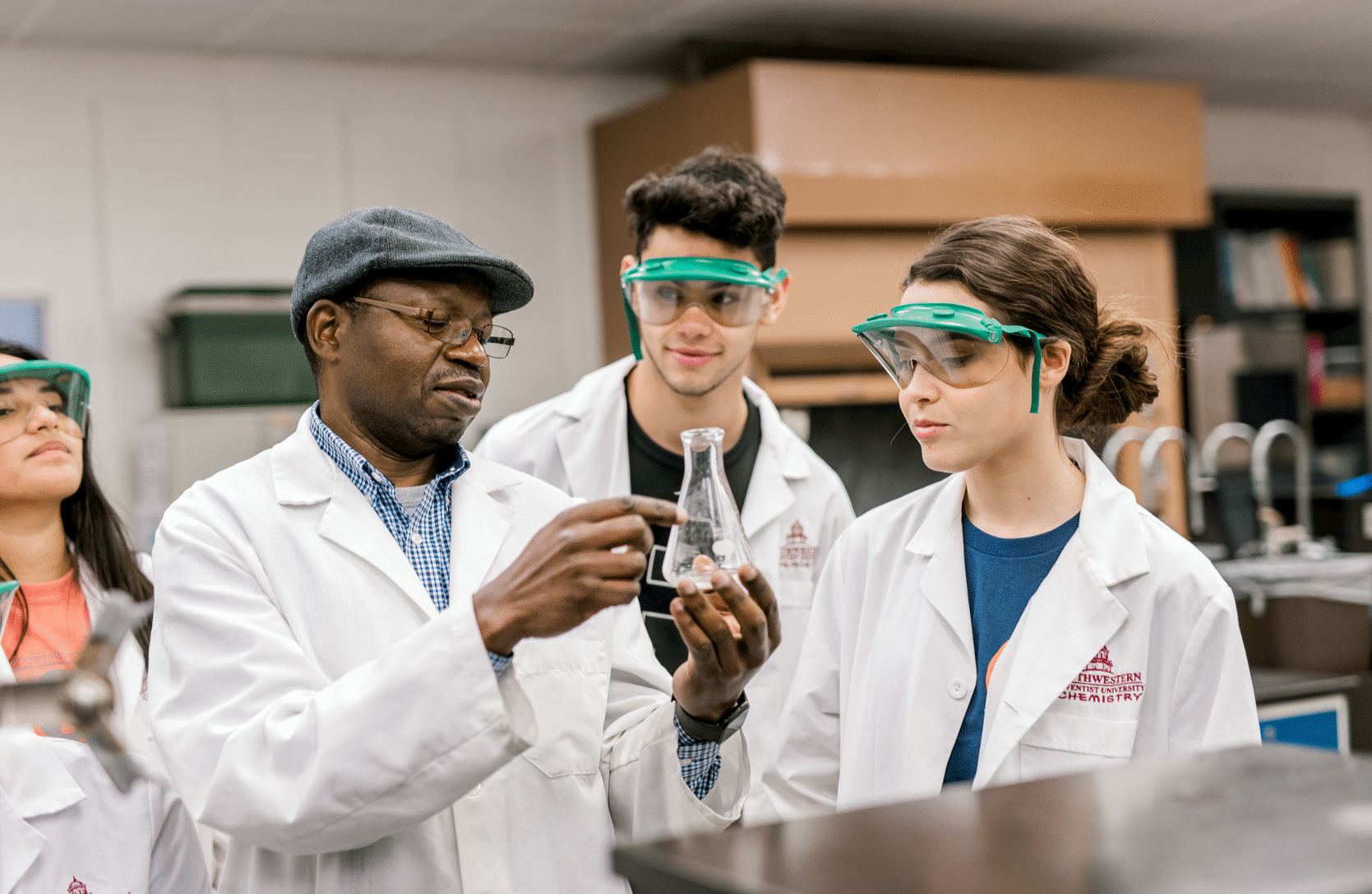 Two students wearing white lab coats and goggles listen to their professor who is holding and pointing to a flask