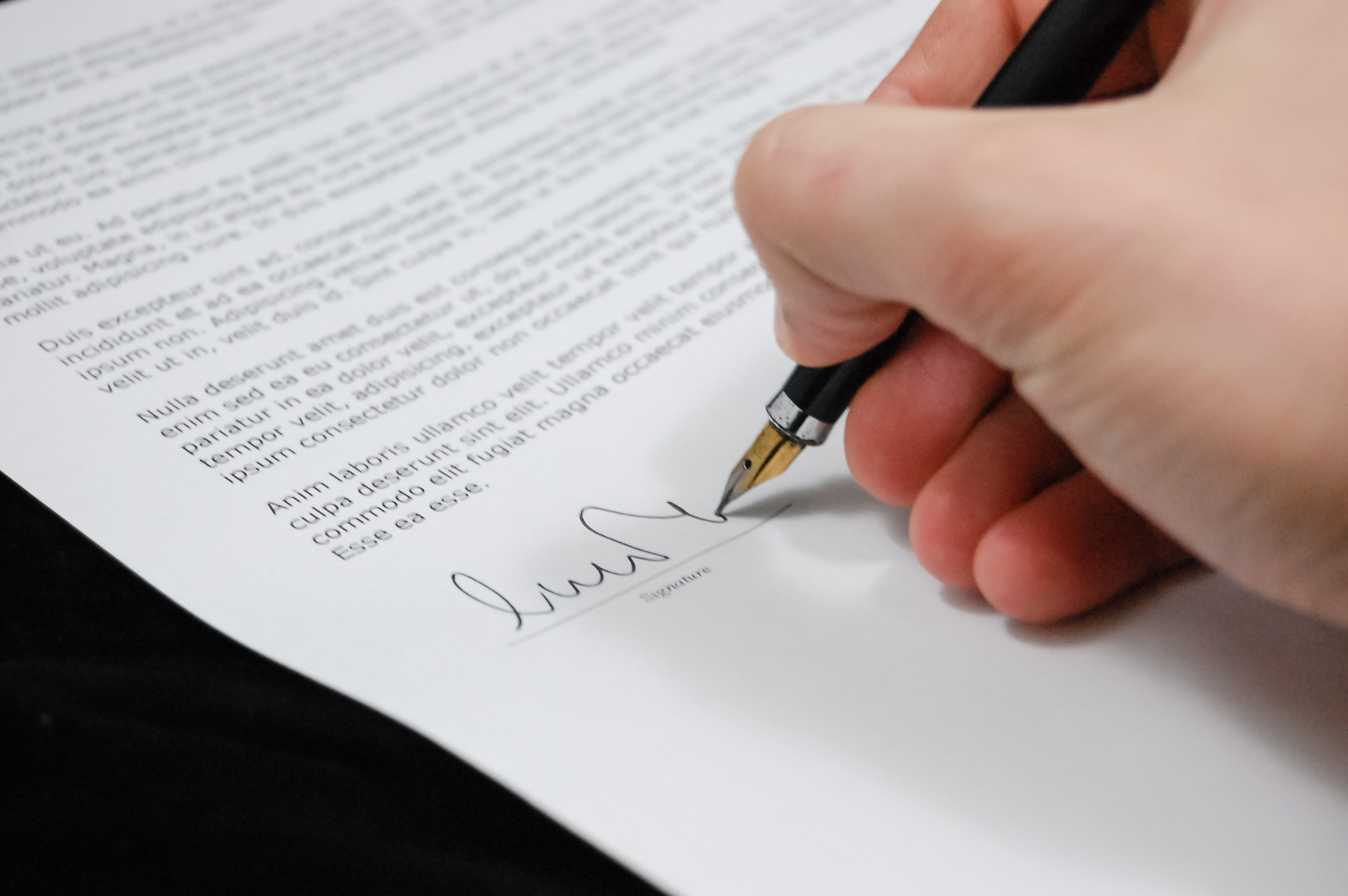 Hand holding pen, signing at the bottom of a document