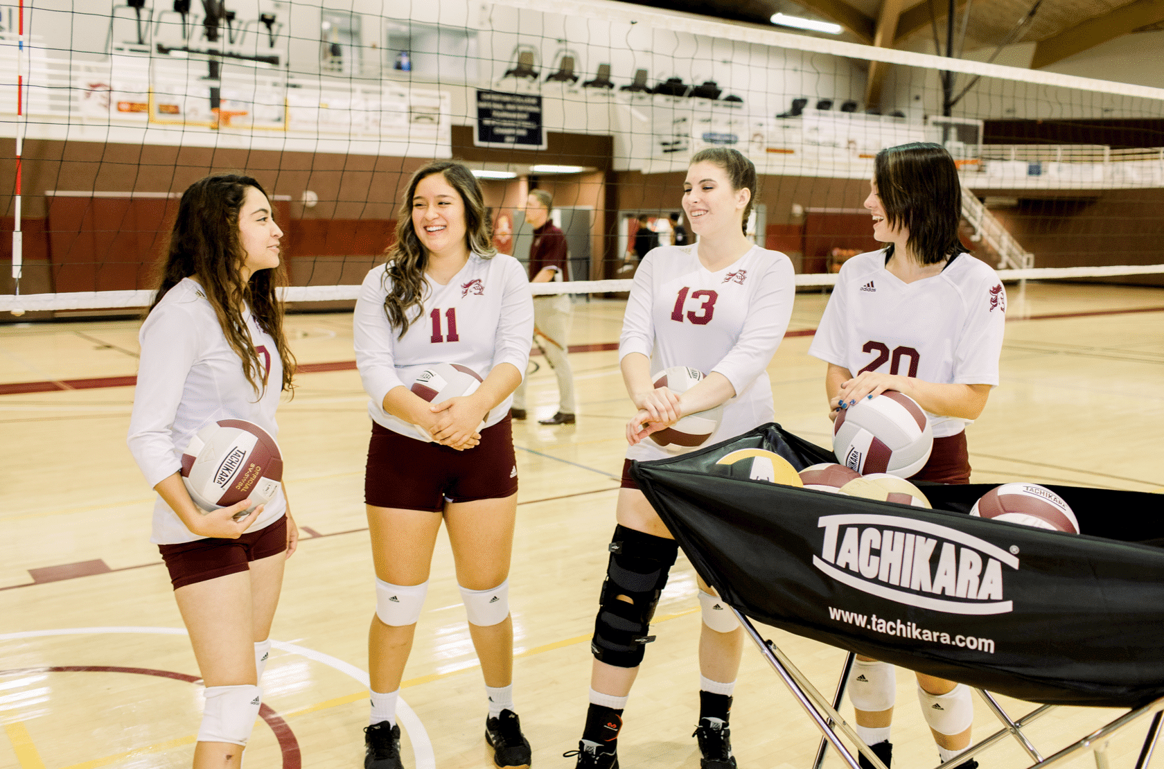 A group of volleyball players stand together talking, in uniform, each holds a volleyball