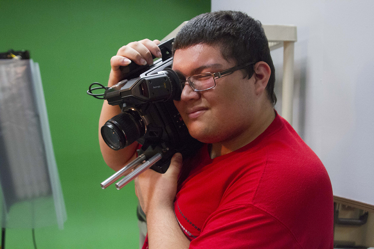 A young man holds a video camera on his should and squints to look through the lense