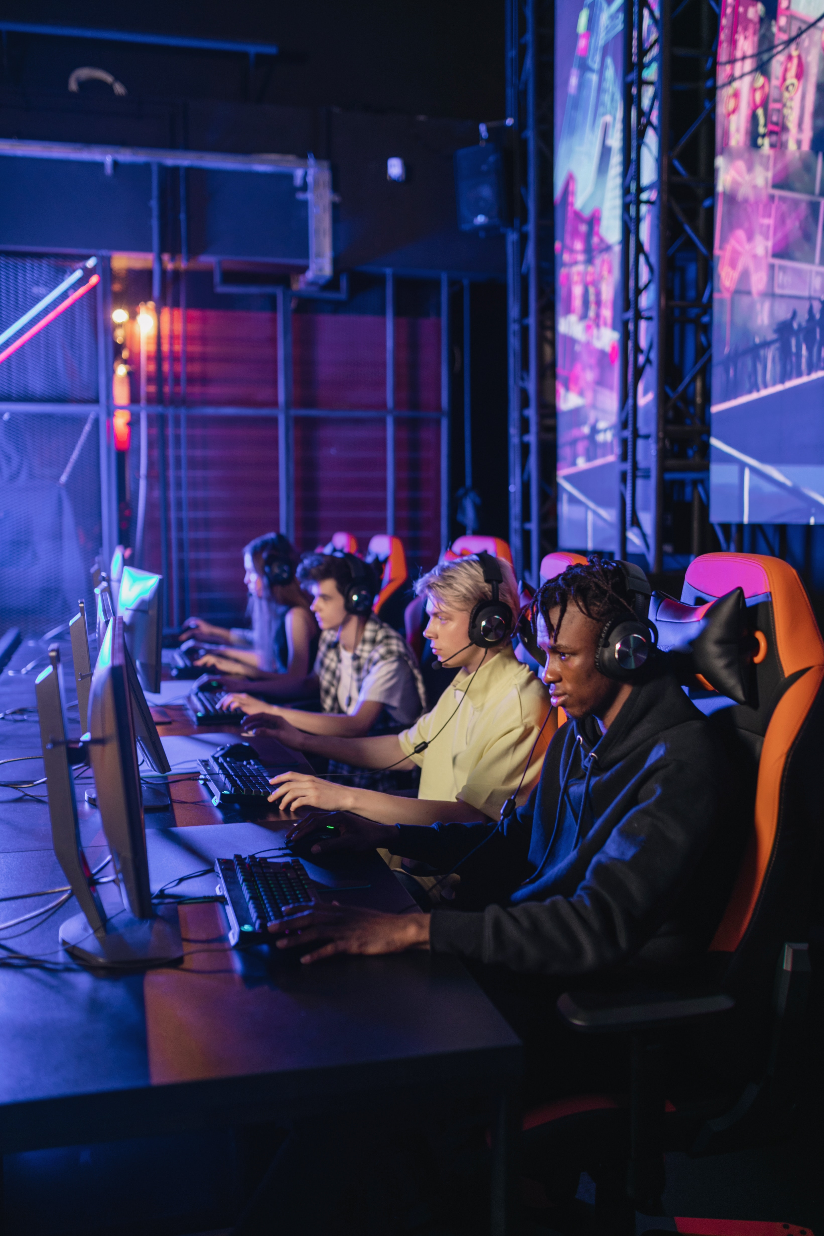 3 men and 1 woman, all wearing large headphones and sitting in gaming chairs in a row, look intently at individual computer screens