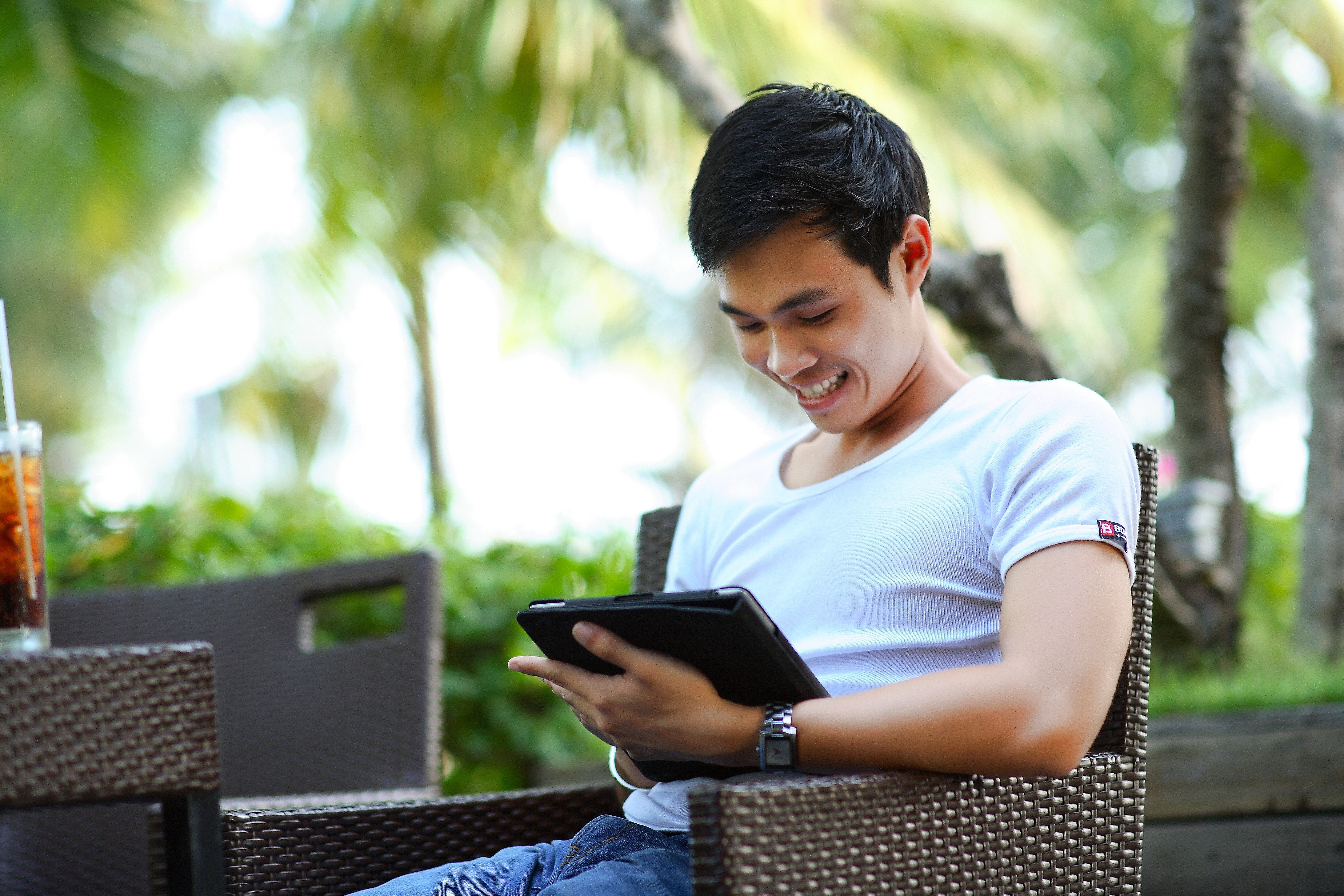 A student smiles as he looks down and smiles while working on his tablet