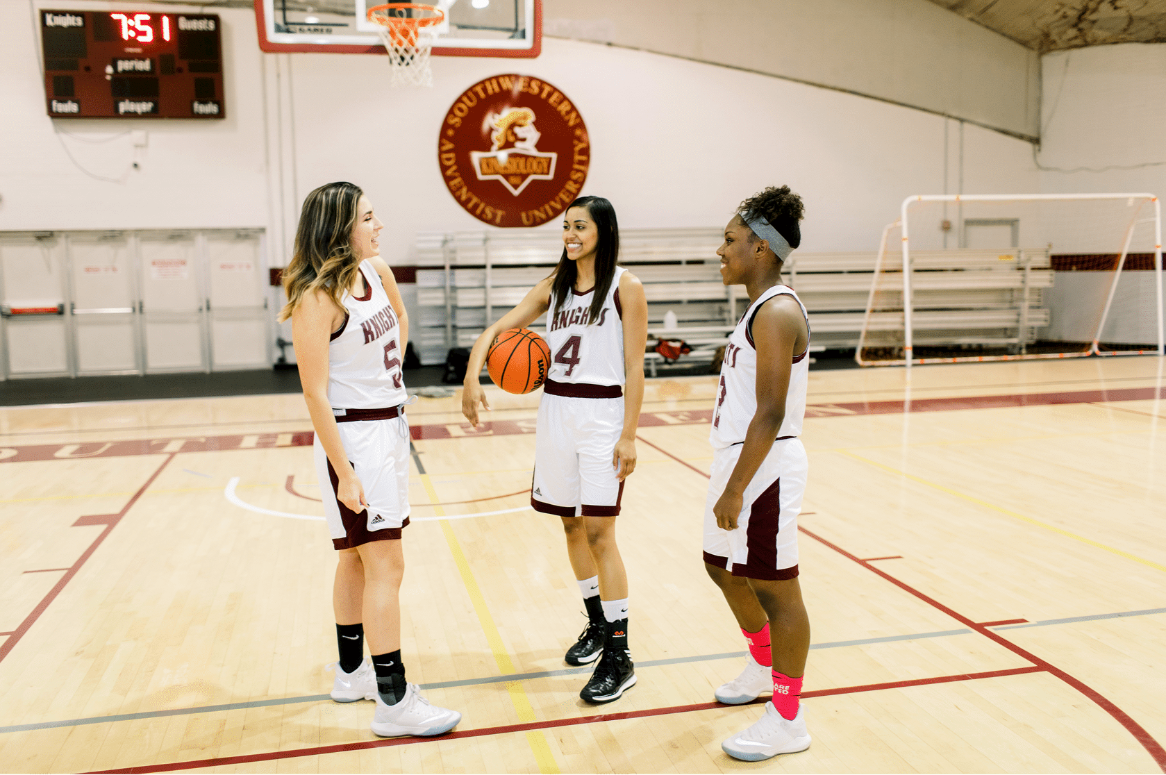 Three female basketball players in uniform stand talking together at the gymnasium, one holds a basketball