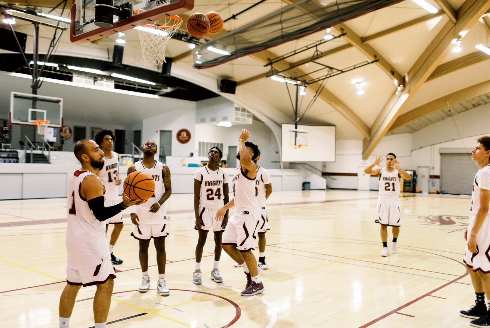 A group of male basketball players gather in the gymnasium wearing their uniforms as thye throw balls into the hoop and look around