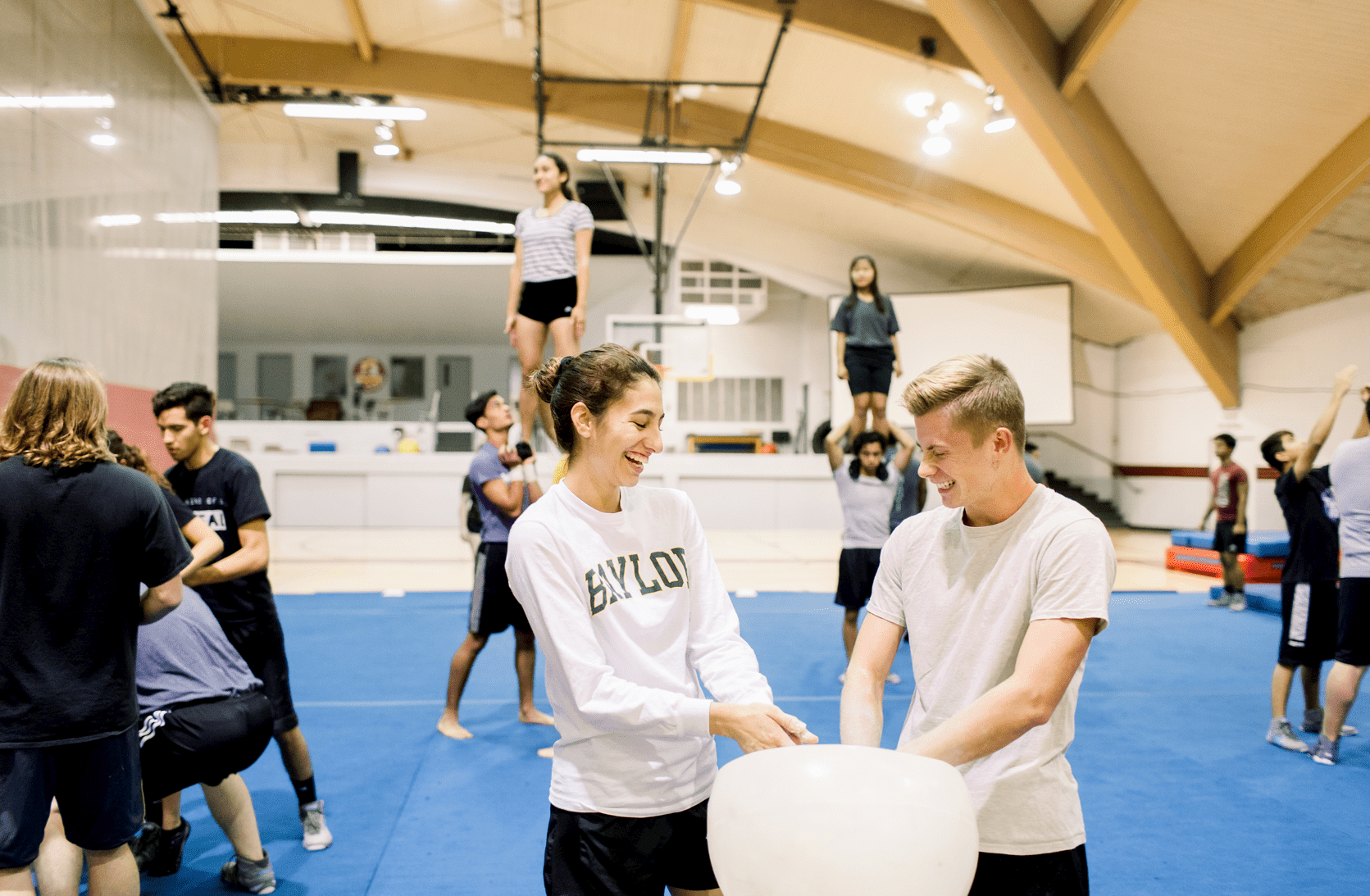 In the gymnasium, the SWAT team practices in the background while we focus on two of the members applying chalk on their hands preparing to practice