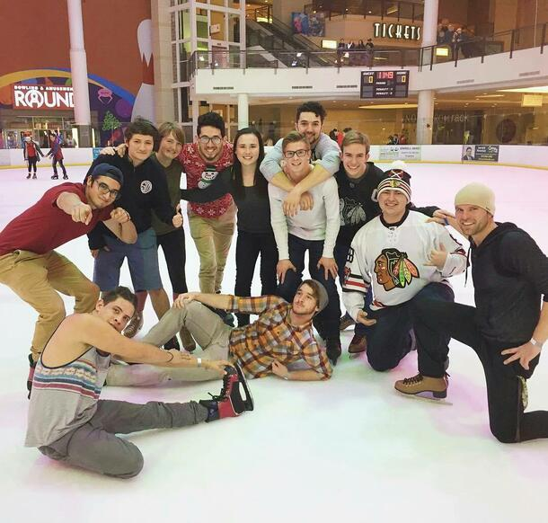 A group of students wearing ice skates stand together on the ice for a group photo
