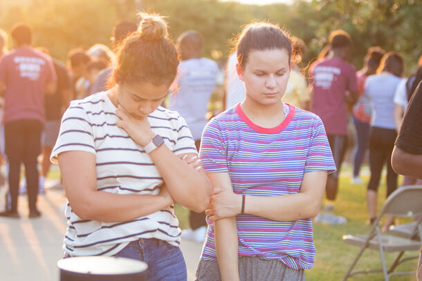 Two students stand near each other and bow their heads to pray.