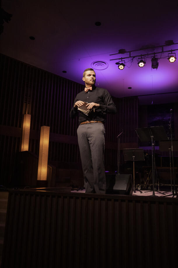 A youth pastor stand on top of a stage and holds his bible as he preaches and looks at the congregation.