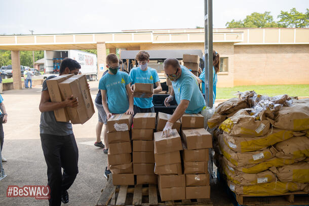 Four people wearing a blue LIFT t-shirt and masks carrying and stacking labeled cardboard boxes of food items