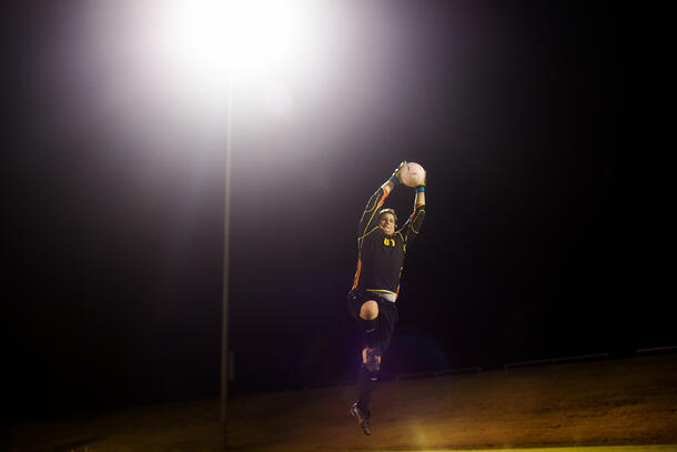 On the soccer field at night, the SWAU Men's goalie jumps up and blocks the ball