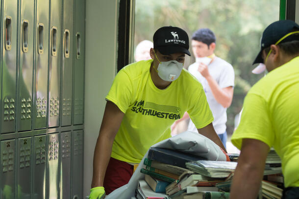 Students, dressed in matching highlight yellow t-shirts, wear white masks as they clean out some lockers