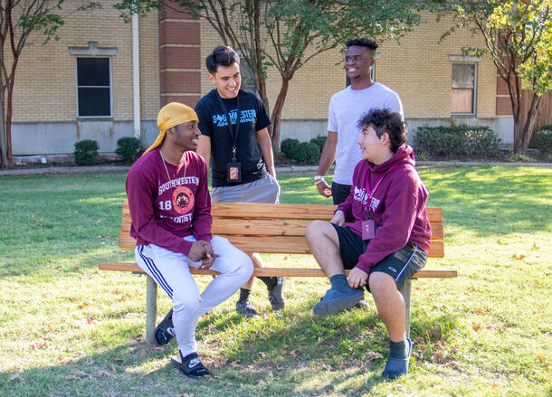 Four male students sit on and around a bench in front of the men's residence hall