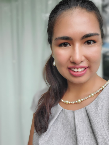 A young woman smiles as she wears pearls and a gray business professional top