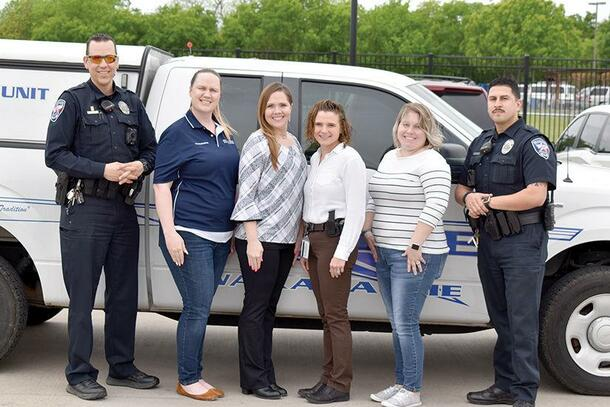 Four women stand in between two officers in uniform and smile in front of a truck