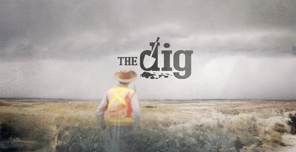 """In a poster promoting """"The Dig"""", a man wearing a bright orange vest stands and looks at the large, rocky land before him"""