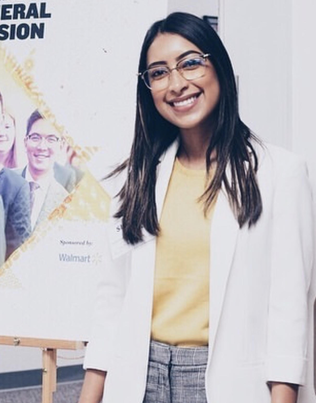A woman wearing a white blazer, gray slacks and a yellow shirt, smiles as she stands in front of an Enactus Poster.