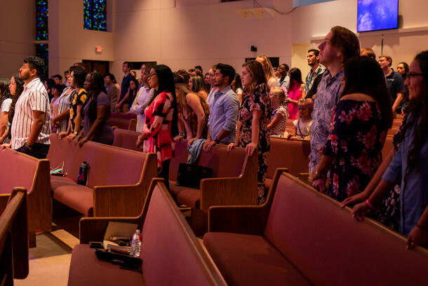 large group of people stands in pews looking toward the left of the photo