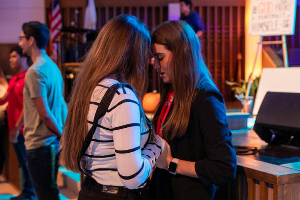 In the Keene Church, two female students hold hands and bow their head as they pray together