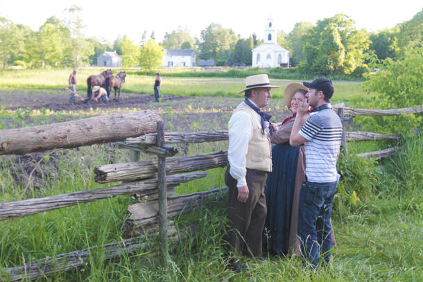 Outside where horses can be seen helping toil the ground, a man and woman stand outside a wooden fence, smiling as they talk to the director
