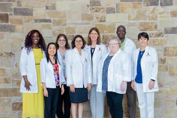 Seven members of the nursing faculty proudly wear their white coats as they stand side by side and smile