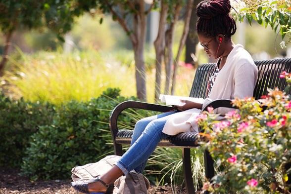 Outside on a bench sits a student with red earphones in as she reads a book