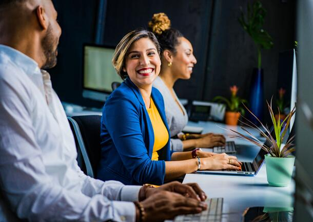Sitting at a long table with other people, a woman smiles at her coworker as she takes a break from typing on her laptop