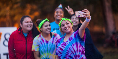Five women gather around in bright shirts as they smile for a selfie