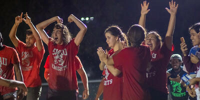 A group of students, matching in red shirts, cheer after a team victory
