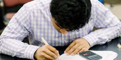 A student looks down and he focuses on completing his test