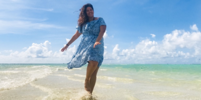 Walking on a beach, a young woman wears a blue dress that blows in the wind