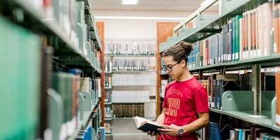 A male student with his hair tied up stands in between the library shelves as he reads through a book