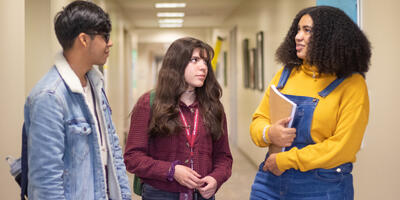A group of three students stop in a hallway as the talk to each other