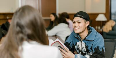 A student smiles as he talks to his peer sitting across from him