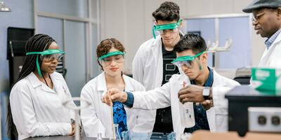 Three students stand to watch their peer conducting an experiment led by their professor standing beside