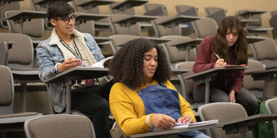 Three students sit down in a large classroom and begin to take notes of the lecture