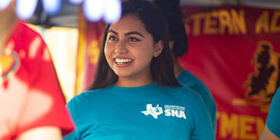 A nursing student, dressed in her blue club shirt, smiles as she explains the nursing club to another student