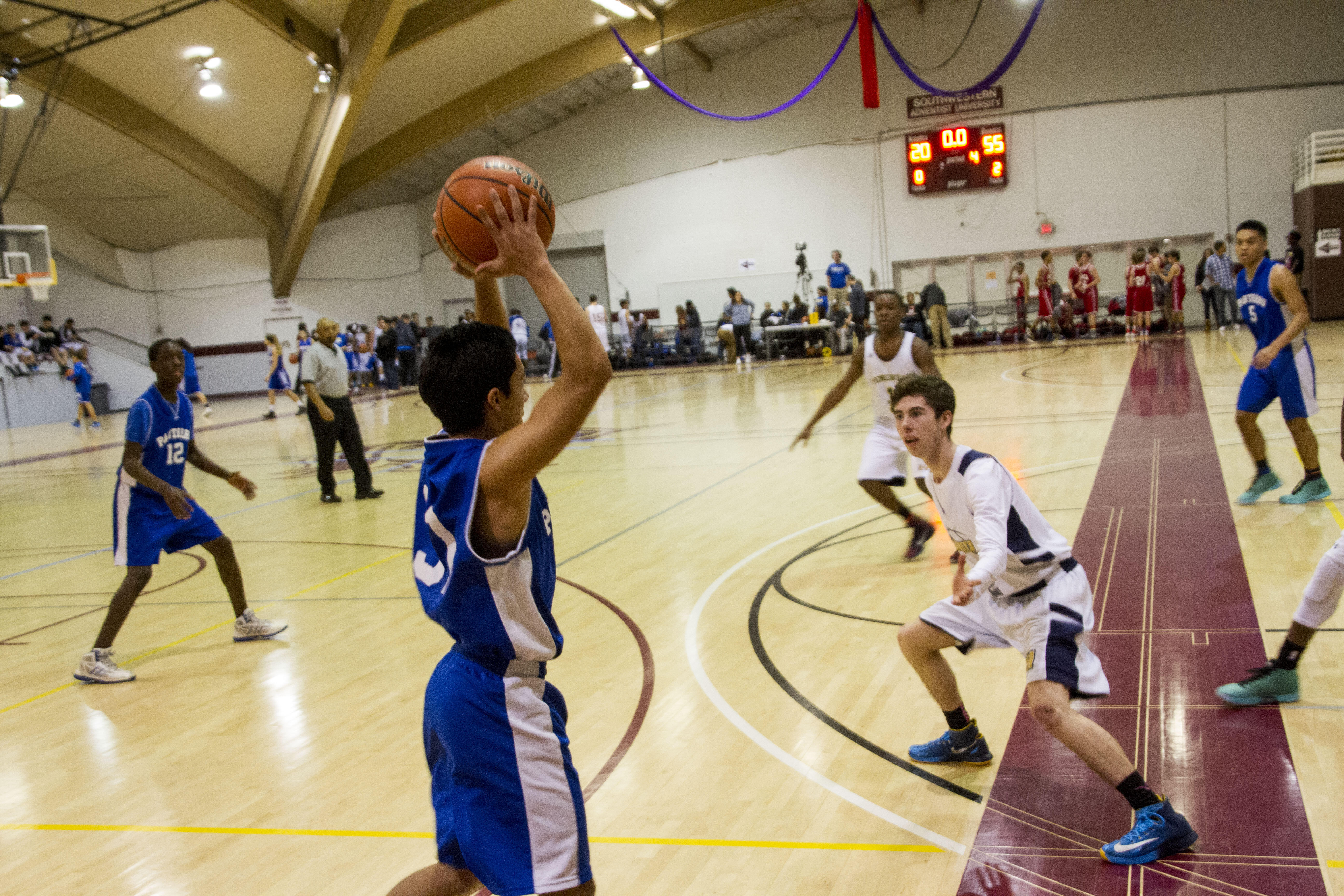 A high school basketball player holds the ball over his head as he looks to see who is open