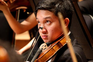 A violinist begins to play while look at the conductor for his cue.