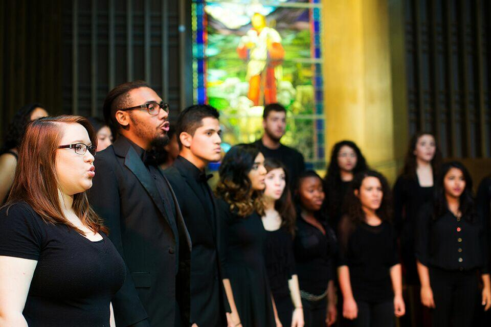 A group of college students wear all black as they sing at the church
